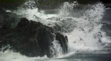 Slow Motion Waves Crash Onto Black Rocks