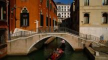 Gondola Passes Under Small Bridge In Venice