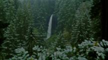 Snow Falls in Forest Surrounding Waterfall