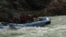 River Raft Full Of People In Rapids