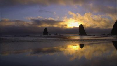 Sunset On Rugged Beach Creates Sea Stack Silhouette