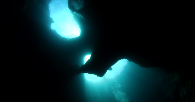 Reveal shot of a Divers in the  Blue Holes Cave, Palau, with light rays, God rays beaming in