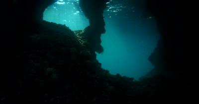 The camera moves through the God Rays shining through a circular swim through hole