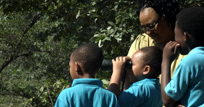 A teacher and three Primary School kids having an outdoor lesson on conservation and using binoculars as an aid