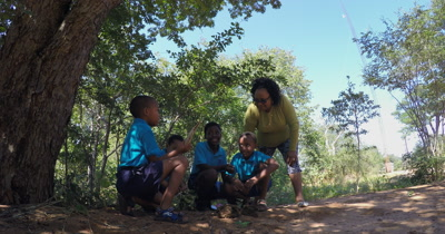 Four Primary School kids and their teacher discussing their thoughts on an animal bone they have discovered