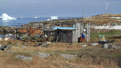 Inuit shed,dog sledges shark meat drying in the sun,dogs resting,ice gergs drifting