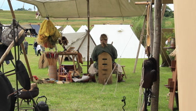 viking trade tent,viking trading weapons and pots and pans,man and wife,the castle of Trelleborg in the background