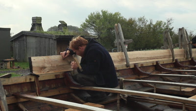 A boatbuilder working at the unfinished pricise copy of the Ladby vikingship.