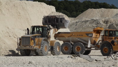 Earth movers working in a limestone quarry