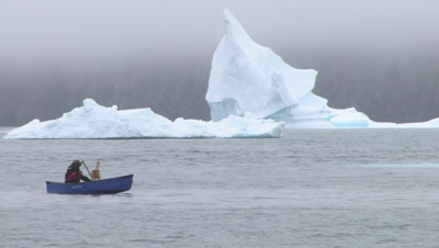 Painter Paddling Away From Iceberg In Canoe, Near Qikitarjuaq, Baffin Island