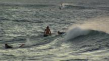 Surfers Floating On Boards At Sunrise