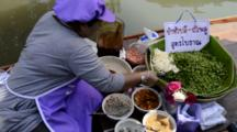 Thailand, Amphawa. Floating Market, Popular Waterfront Market Where Vendors Sell Goods From Longboats. Woman Mixing A Salad With Greens, Curry Paste, Dried Fish, Onions & Spices. (UR)