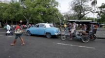Havana, Cuba. Street Scene. Old Cars, Pedestrians And Pedi Cabs.