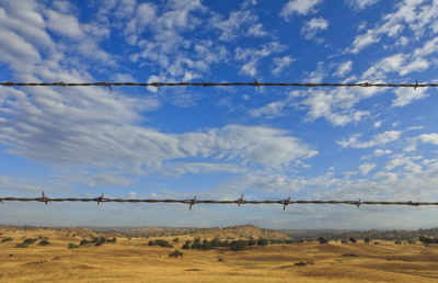 Clouds timelapse with barbed wire fence