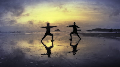 Couple practicing yoga on beach at sunset,Port Orford,OR