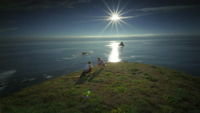 Couple practicing yoga on hillside overlooking Pacific Ocean,OR