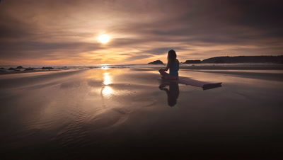 Woman practicing yoga on beach at sunset on Oregon Coast