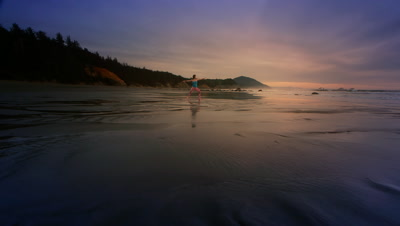 Woman practicing yoga on beach at sunset on Oregon Coast