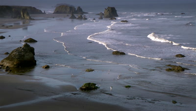 Pacific Ocean beach with rolling waves and man jogging