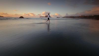 Teen boy jogging on beach,Pacific Coast,Oregon