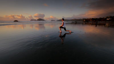 Teen boy stretching and loosening up before running,Pacific Coast,OR