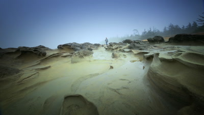 Woman walking among sandstone formations by Pacific Coast,OR