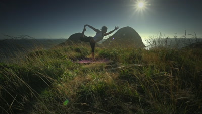 Woman practicing yoga on hill overlooking Pacific Ocean,Oregon