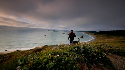 Man hiking with dog on trail overlooking Pacific Ocean,Oregon