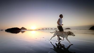 Boy running with his dog,Bandon,Oregon
