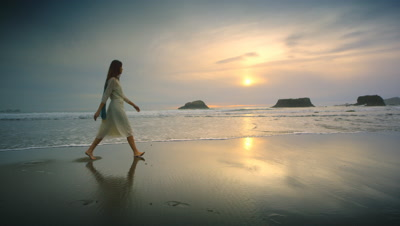 Young woman walking beach at sunset Port Orford OR