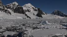 Gliding Over Water & Ice Reflecting Antarctic Mountain Shoreline On Mirror Smooth Sea