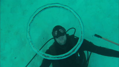 Diver Blowing Abstract Air Bubble Ring In Underwater Light Patterns