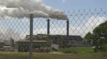 Vapor Emissions Belching From Sugar Mill Behind Fence