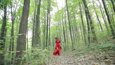 Steadicam shot of a beautiful fairy tale girl in red long dress running in woods