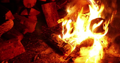Midnight bonfire or campfire firewood and people in the background outdoors