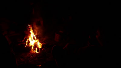 People sitting around of fire in night and talking