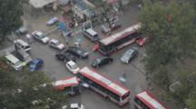 Time Lapse Looking Down On Traffic At A Busy Intersection In Beijing China. Cars, Busses, Trucks And Pedestrians With Umbrellas.