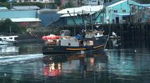 Fishing Boat Returning To Port. And Fish Processing Plant