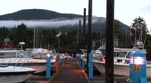 Low Clouds Over Fishing Boats And Coastal Community Boat Harbor.
