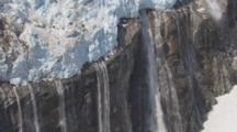 Aerial Cineflex Over Hanging Glacier Dramatic Mountain Landscape Waterfall Flows From Under Ice Cascading Down Rocky Cliff Face Melting Glacier