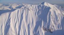 Aerial Cineflex Tilt Up Dramatic Snow Covered Cliffs To Wide Shot Of Wrangell St. Elias Mountain Range Beautiful Light
