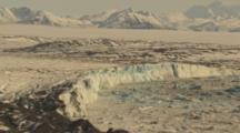 Aerial Cineflex Pull From Blue Face Of Glacier To Bleak Moonscape Icefield Mountains