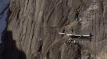 Small Bush Plane Flies In Front Of Massive, Snow-Capped, Rugged Mountain In Alaska Range, Zoom To Plane In Front Of Near-Vertical Rock Face. Denali National Park Zatzworks Cineflex.