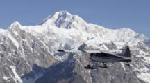 Flightseeing Bush Plane Enters Frame And Flies Just Below Mountain Peak Level Of Rugged Rocky Alaska Range, Snow Covered Mount Mckinley Rises Above Other Peaks. Zatzworks Cineflex Aerials Danali National Park.