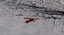 Bush Plane From Above Flies Over Glacier Field And Steep Rocky Mountains, Pull Back To Reveal Massive Snow-Covered Near Vertical Faces Ridges Peaks Couloirs Valley Glaciers Of Alaska Range. Zatzworks Cineflex Aerials Danali National Park.