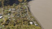 Medium Shot Of Rooftops And Roads Among Windblown Trees, Pull Back To Reveal Interior Alaska Village Of Ruby Along Muddied Mighty Yukon River Flowing Through Boreal Forest. Cineflex Alaska Aerial By Zatzworks