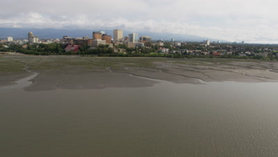 Low POV Aerial Over Water Tilt to Reveal then fly over City of Anchorage,alaska