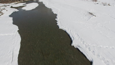 Low POV Aerial Over Frozen River In Snowy Mountain Range