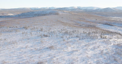 Aerial Flat,frozen inhospitable landscape,with mountain range in distance
