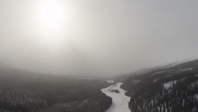 Aerial POV Over Frozen River Lined by Forest,alaska